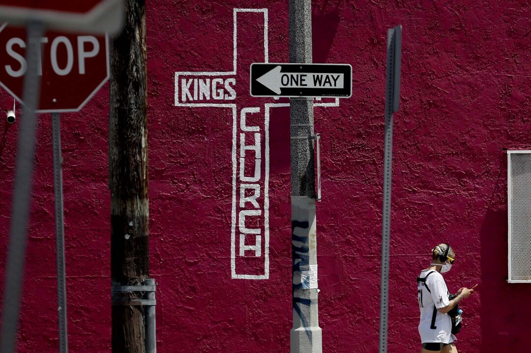 A woman walks past a storefront church on Vermont Avenue. L.A. area churches have been closed since late March to help prevent the spread of cornonavirus.