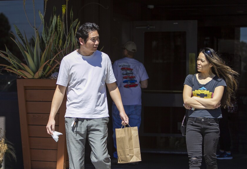 Matthew Wu and Toni Ann Moore leave the Recess Room restaurant in Fountain Valley after receiving a free lunch Friday.