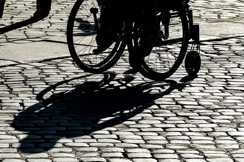 A wheelchair-bound person casts a shadow in central Rome.