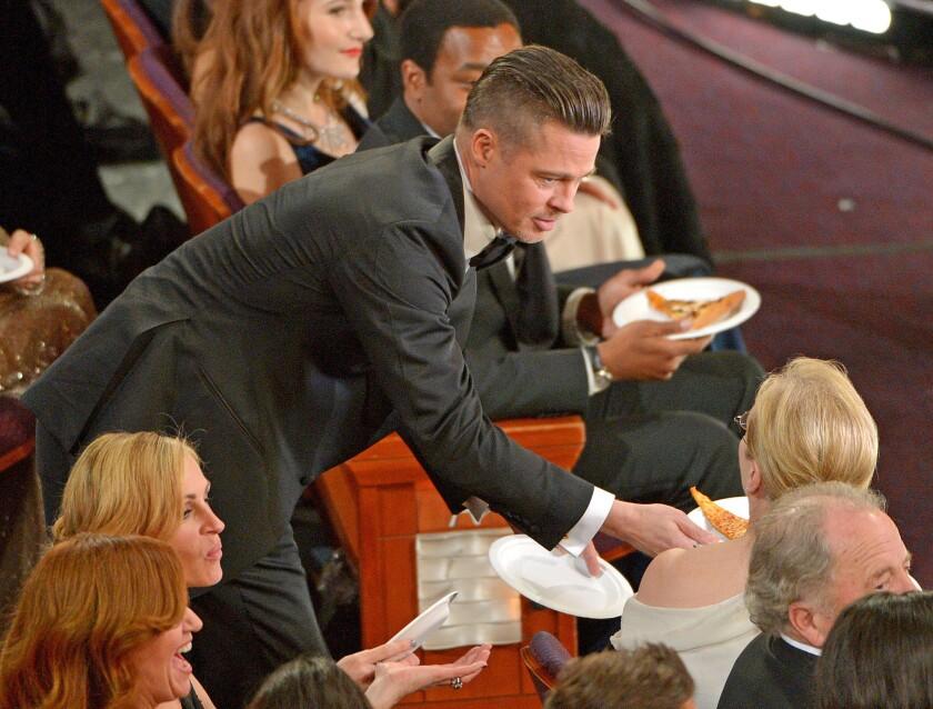 Brad Pitt offers Meryl Streep pizza.