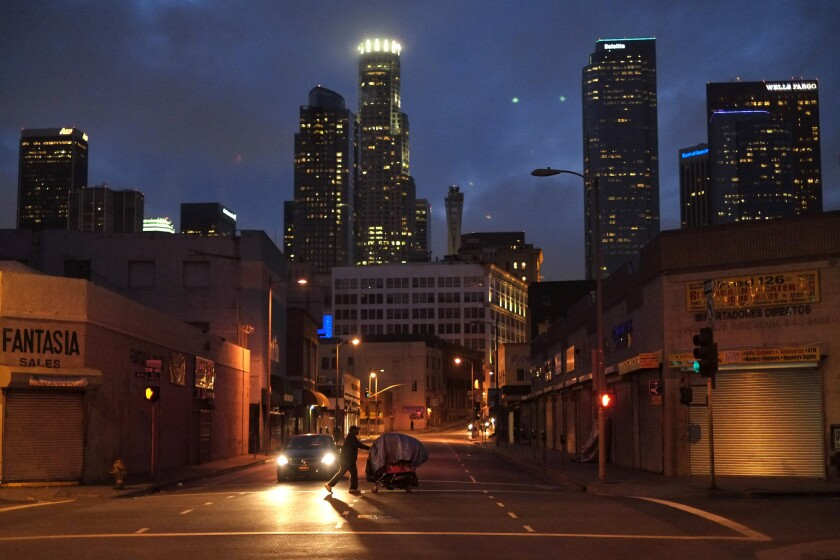 A federal appeals court panel appeared skeptical about a Los Angeles city ordinance that bans people from living in their car. Above, a homeless resident pushes a cart along a downtown street.