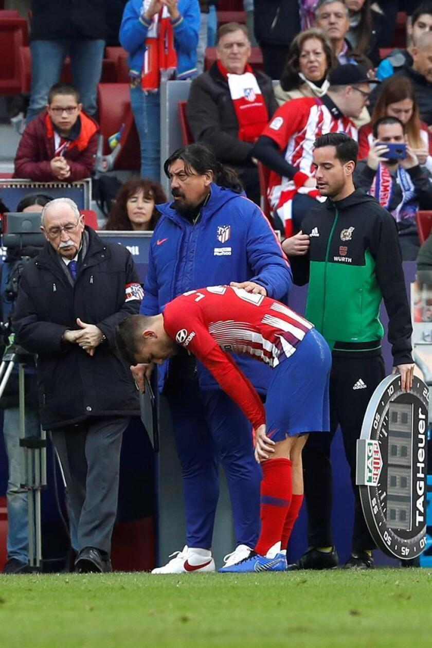 El jugador del Atlético de Madrid Lucás Hernández, que se ha lesionado una rodilla durante el partido que hoy disputa su equipo frente al Alavés en el estadio madrileño Wanda Metropolitano asistido por el segundo entrenador, Germán Burgos. EFE