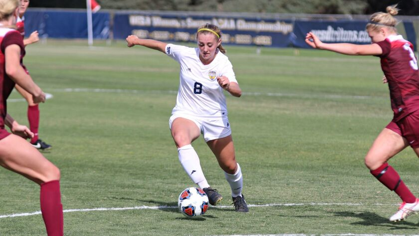 UCSD forward Mary Reilly (8) dribbles between Azusa Pacific defenders in the Tritons' 4-2 victory in the NCAA Division II playoffs. Reilly scored two goals.