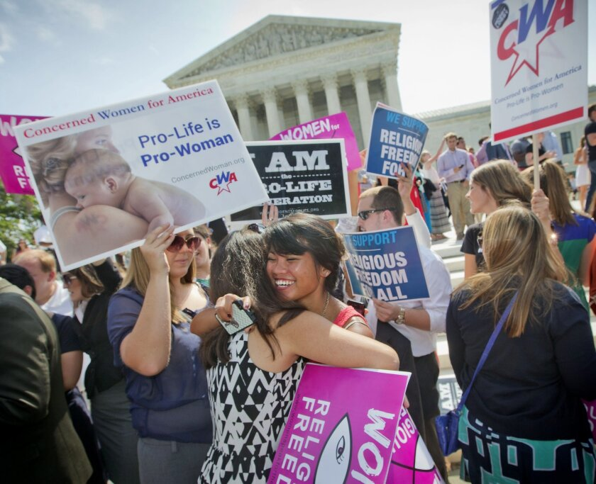 Demonstrators embrace as they react to hearing the Supreme Court's decision on the Hobby Lobby case outside the Supreme Court in Washington, Monday, June 30, 2014. The Supreme Court says corporations can hold religious objections that allow them to opt out of the new health law requirement that the