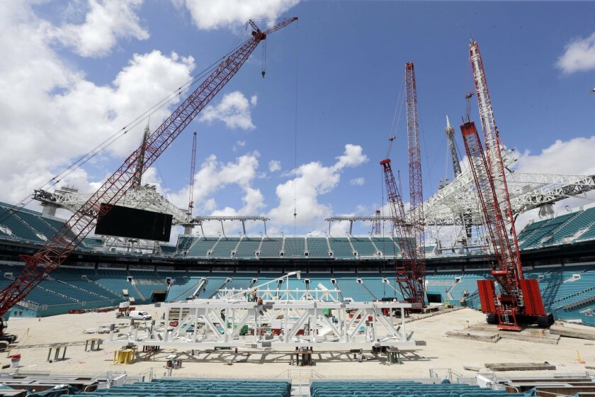 Workers assemble trusses in the center of the field that will support a 530,000-square-foot canopy at the Miami Dolphins' NFL football stadium, Thursday, June 2, 2016, in Miami Gardens, Fla. The first game of 2016 is three months away, and the stadium is far from ready. But Dolphins officials say t