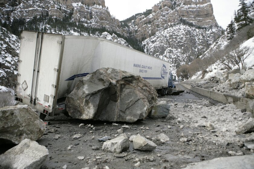 In this Tuesday, Feb. 16, 2016 photo provided by the Colorado Department of Transportation, fallen boulders rest against a damaged tractor-trailer after a Monday rock slide on Interstate 70 in Glenwood Canyon in western Colorado. Closures remained in effect on Interstate 70 on Wednesday, Feb. 17. (