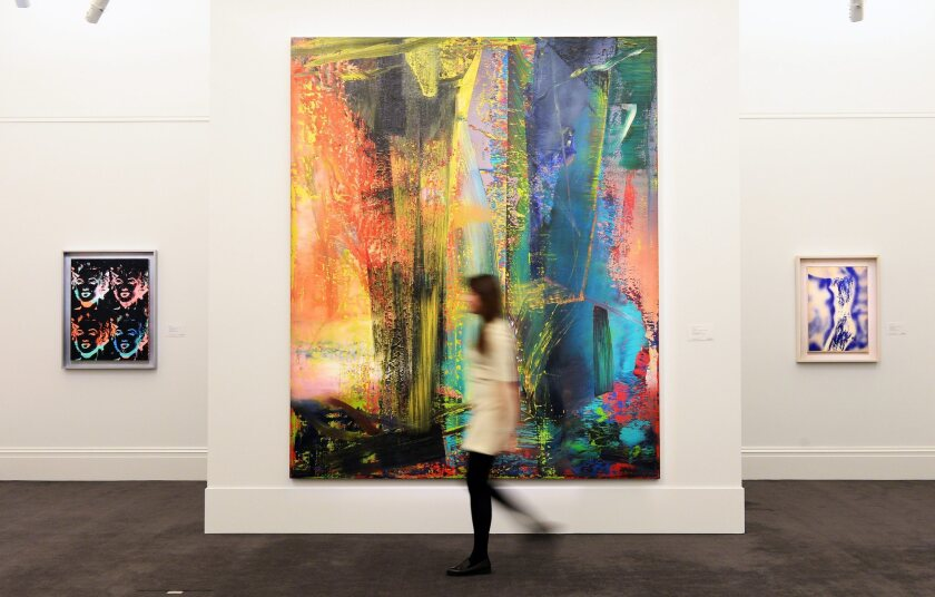 "A Sotheby's staff member walks past Gerhard Richter's ""Abstraktes Bild,"" which sold for more than $46 million this week after going for just $607,500 in a 1999 auction."