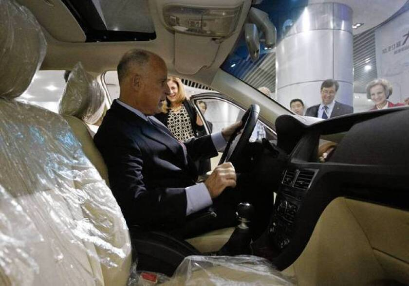 California Gov. Jerry Brown sits in an electric car during a visit to the Shenzhen, China, headquarters of automaker BYD on Tuesday.