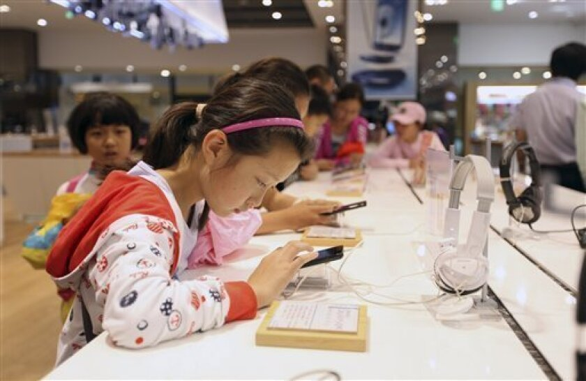 Chinese children try out Galaxy smartphones at Samsung's showroom in Seoul, South Korea (AP Photo/Hye Soo Nah)