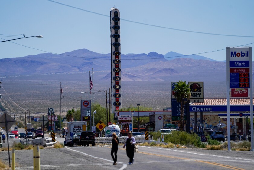 People cross Baker Boulevard, with the town's landmark 134-foot-tall electric thermometer in the background.