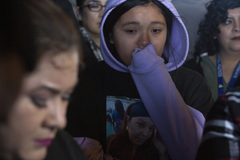 Angela Rodriguez, 11, daughter of Kiesha Saravia, listens to her grandmother speak during a news conference