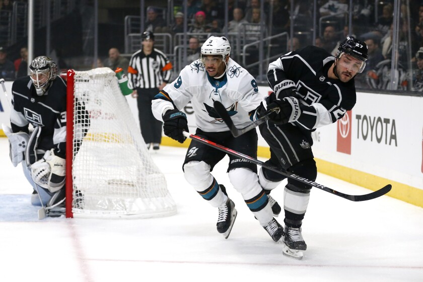 Kings defenseman Alec Martinez, right, passes the puck as San Jose's Evander Kane defends Monday at Staples Center.