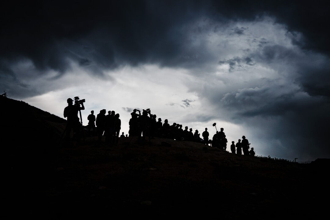 Troops and journalists are silhouetted on a hilltop