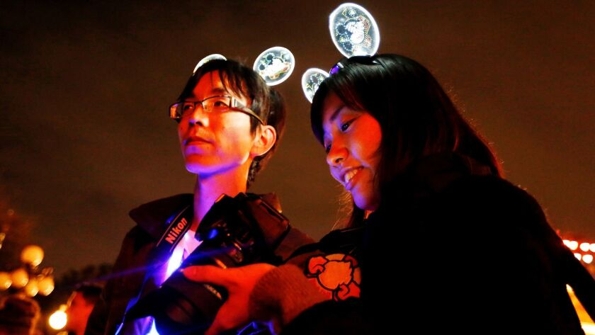 Shinya Yoshida, left, and Akiko Shiho, both of Tokyo, wear acrylic glow Mickey Mouse headbands to commemorate the return of the Main Street Electrical Parade.