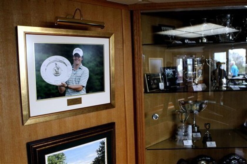 A picture of  golfer Rory McILroy  hangs on the wall beside the trophy cabinet at McIlroy's home club Holywood Golf Club   situated on the outskirts of Belfast, Northern Ireland, Sunday, April, 10, 2011,   Rory McILroy plays in the Masters Golf Championship in Augusta, Georgia.  (AP Photo/Peter Mor