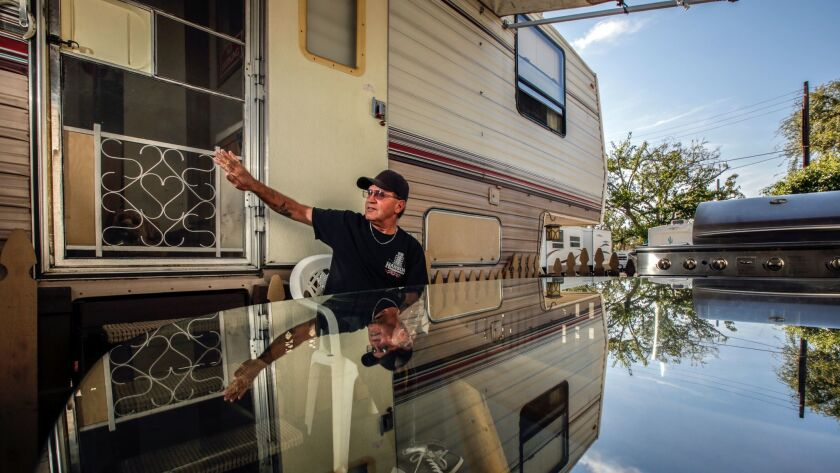 A resident of the Los Angeles County Fair Assn. trailer park stands in front of his mobile home in Pomona, Calif. on Nov. 12, 2015.