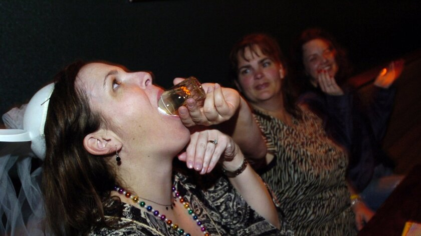 Bride-to-be Amy Noga takes a shot with a little help from her friend Kate Rascon on the night of her bachelorette party in Santa Rosa in 2006. The cost of gifts, travel and other items for some wedding guests can come to hundreds of dollars.