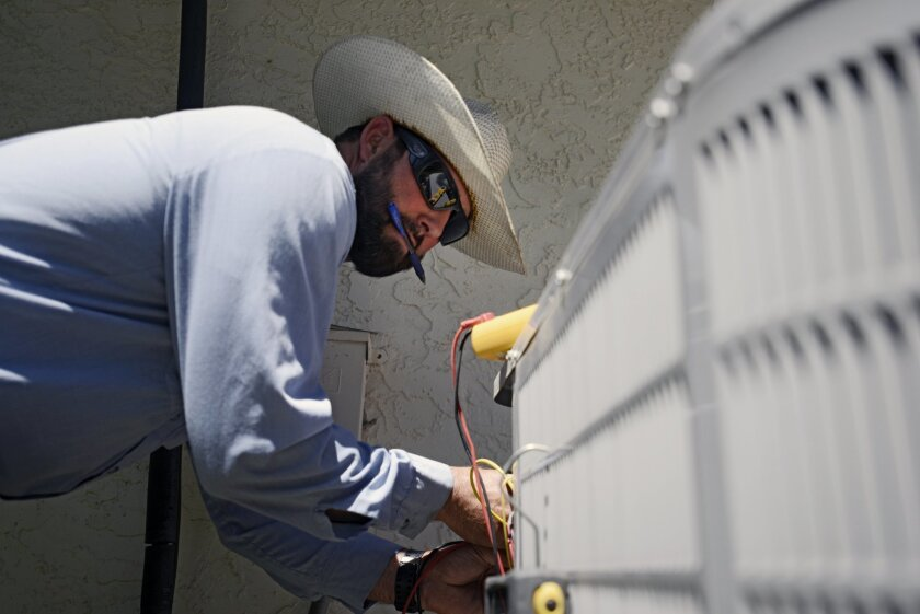 Josh Salow checks to see if an air conditioning unit is working at a home in Tempe, Ariz., on Thursday June 2, 2016. Salow said summer is the busiest season for AC repairs, and he fixes roughly three to four units a day in summer months. Parts of the Western U.S. are getting an early taste of scorc