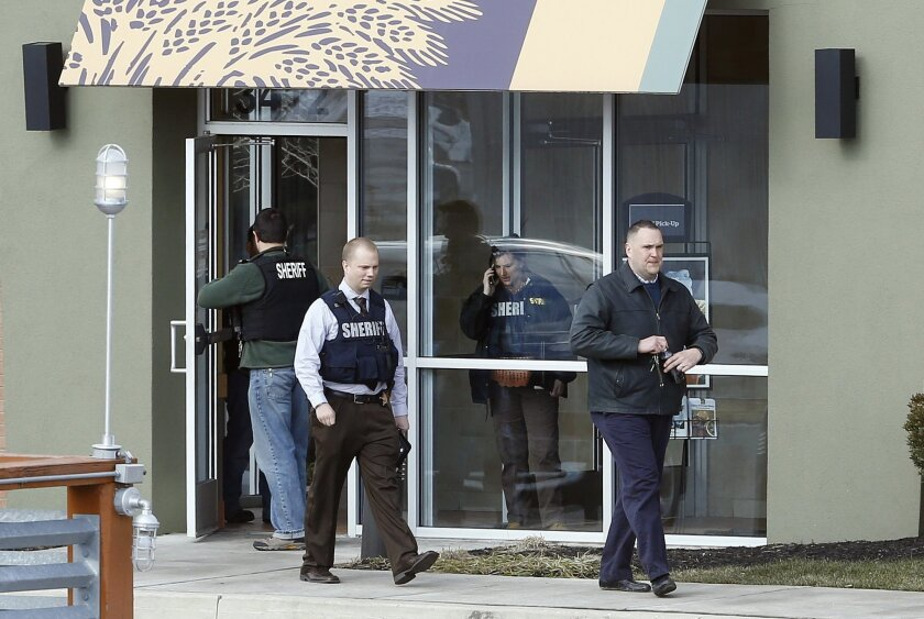 Investigators walk at the scene of a shooting at a shopping center in Abingdon, Md., Wednesday, Feb. 10, 2016. A man opened fire inside a shopping center restaurant during lunchtime. (AP Photo/Patrick Semansky)