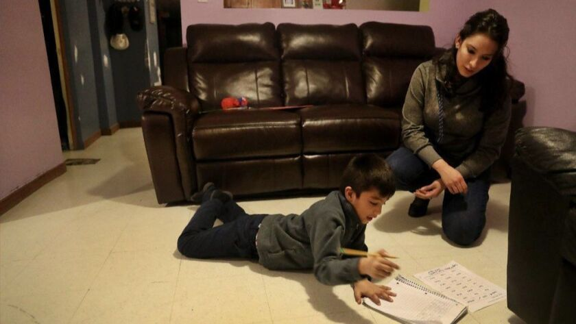 Adriana Alvarez, right, helps her son Manny, 6, with his homework at their Cicero home on Feb. 20, 2019.
