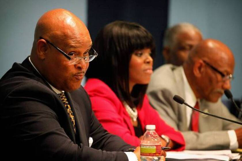 Omar Bradley, left, speaks at a mayoral candidates forum in March. Next to him is Aja Brown.
