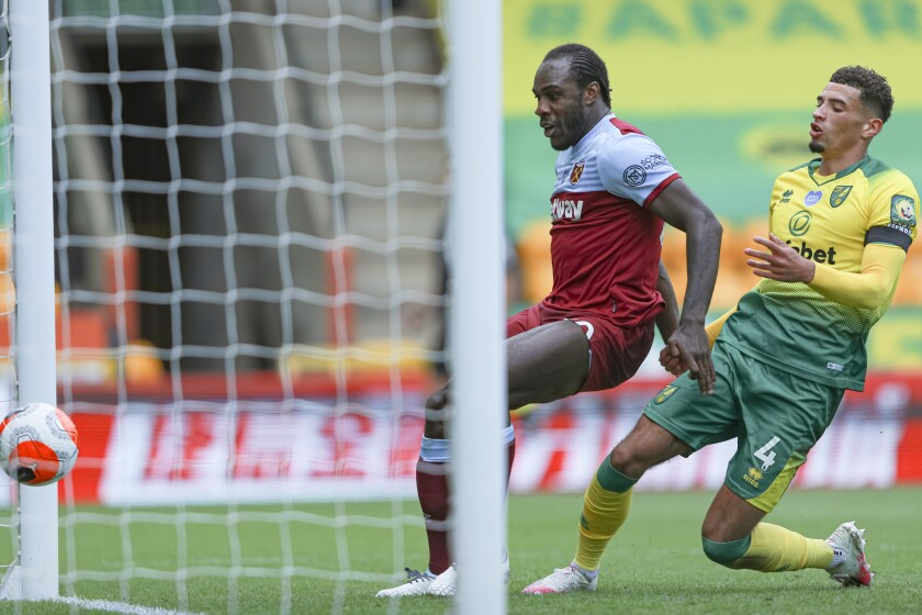 West Ham's Michail Antonio, left, scores his side's third goal, next to Norwich City's Ben Godfrey during the English Premier League soccer match between Norwich City and West Ham at the Carrow Road stadium in Norwich, England, Saturday, July 11, 2020. (AP Photo/Ian Walton, Pool)