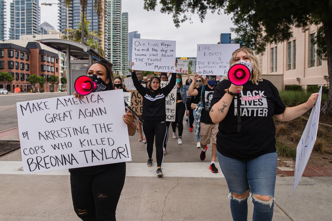 """Bethany Unwin and Kelsey-Rae Jones lead a """"Girls March"""" through downtown on June 20, 2020 in San Diego, California."""