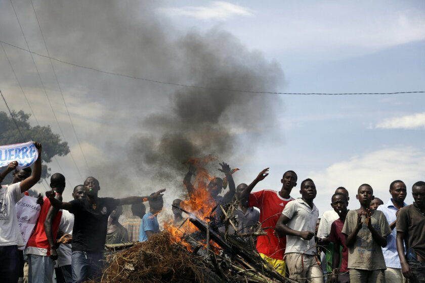 Demonstrators face soldiers in the Musaga neighborhood of Bujumbura, Burundi, Monday May 18, 2015. The unit temporarily withdrew. The army has deployed throughout the town as hundreds return to the streets Monday to protest the president's decision to seek a third term in office. ( AP Photo/Jerome Delay)