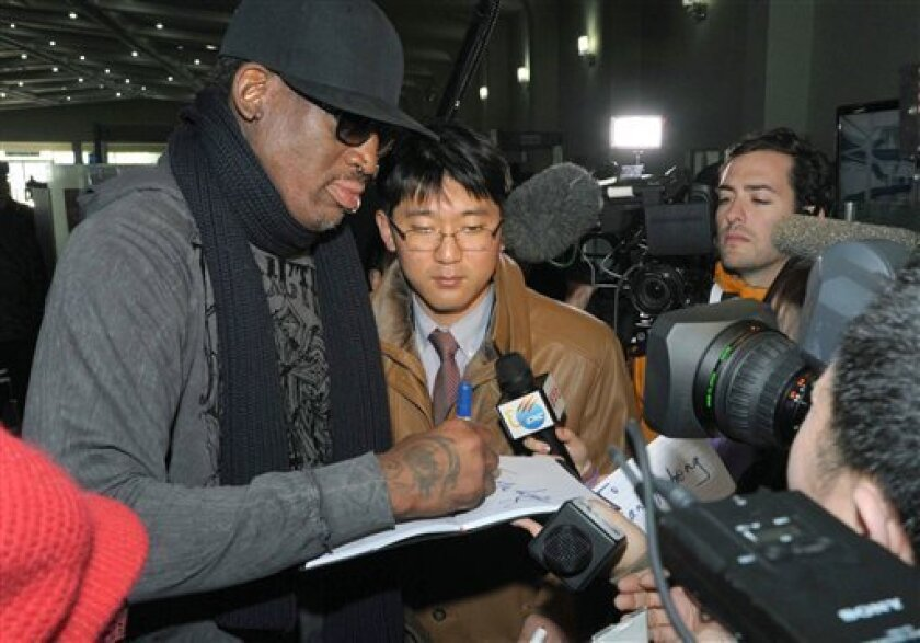 """Former NBA star Dennis Rodman signs his autograph for a fan at the Pyongyang Airport in Pyongyang, before he leaves North Korea Friday, March 1, 2013. Ending his unexpected round of basketball diplomacy in North Korea on Friday, Rodman called leader Kim Jong Un an """"awesome guy"""" and said his father and grandfather were """"great leaders."""" (AP Photo/Kyodo News) JAPAN OUT, MANDATORY CREDIT, NO LICENSING IN CHINA, HONG KONG, JAPAN, SOUTH KOREA AND FRANCE"""