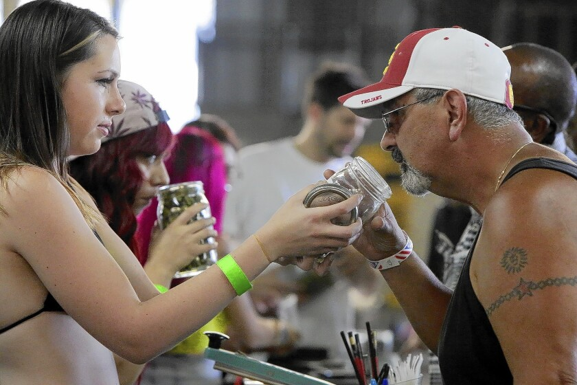 Vendor Drina Oliver offers a jar of cannabis so a shopper can smell the quality at the event organized by West Coast Collective, a marijuana dispensary in Boyle Heights.