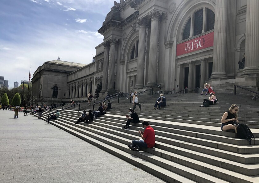 People sit outside the Metropolitan Museum of Art on Saturday, May 2, 2020 in New York. New York City police dispatched 1,000 officers this weekend to enforce social distancing to prevent the spread of coronavirus, as warmer weather tempted New Yorkers to come out of quarantine. (AP Photo/Ron Blum)