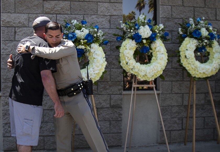 CHP officers embrace at a memorial