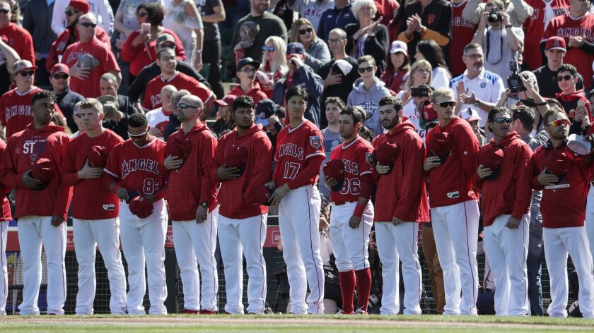 Angels players stand during the National Anthem before a game against the Milwaukee Brewers at Tempe Diablo Stadium last year in Tempe, Ariz.