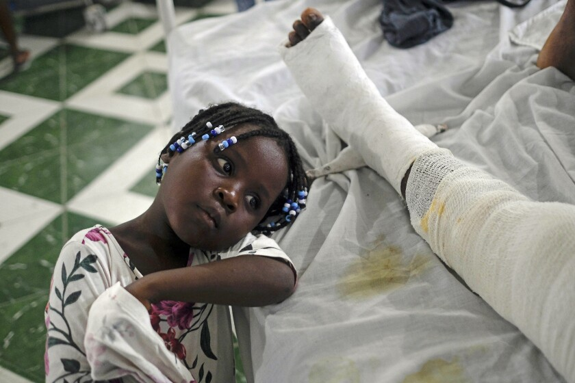 At the hospital in Haiti, a little girl rests next to her mother, who was injured in the earthquake