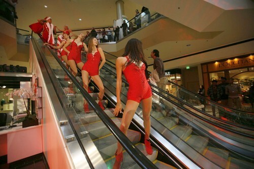 Hunky Santa and the Candy Cane Girls come down the escalator at the start of their performance at the Beverly Center.
