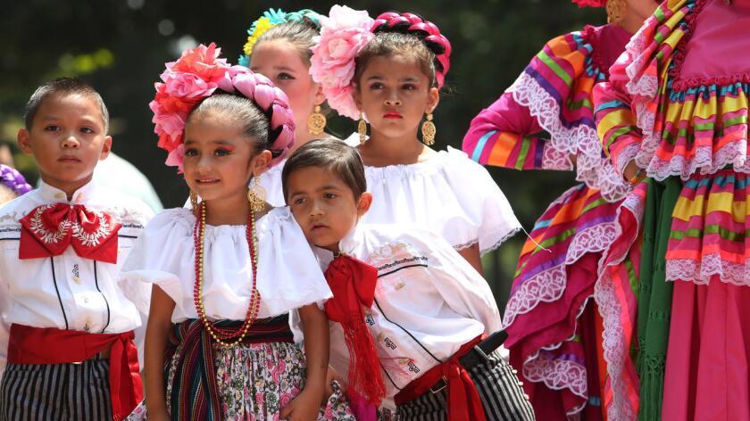 Miembros de un grupo folclórico 'Nuevo Amancer' esperan el momento de su participación en la celebración de la ciudad de Los Ángeles.