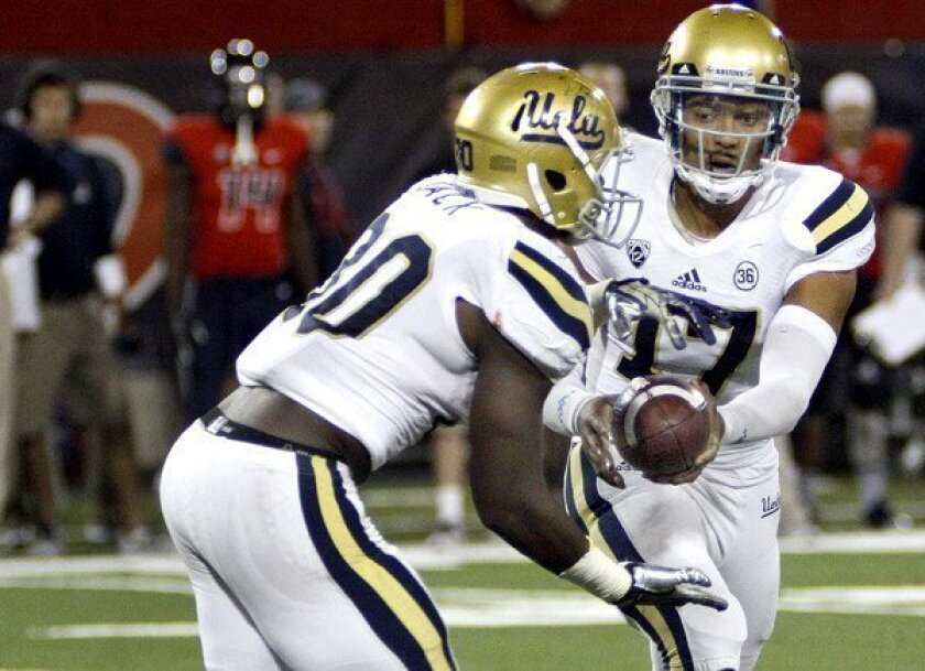 UCLA quarterback Brett Hundley hands the ball to Myles Jack during the second half of the Bruins' 31-26 win over the Wildcats on Saturday.