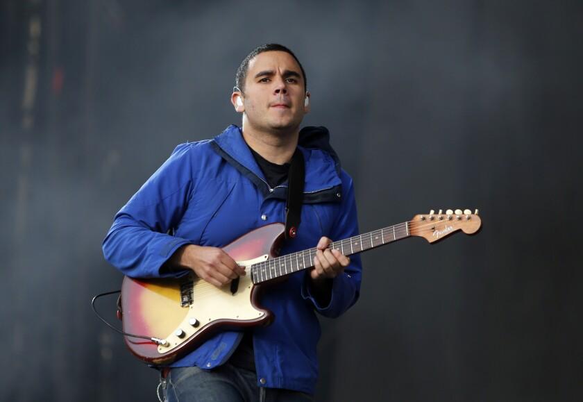 Rostam Batmanglij, wearing a blue jacket, plays the electric guitar.