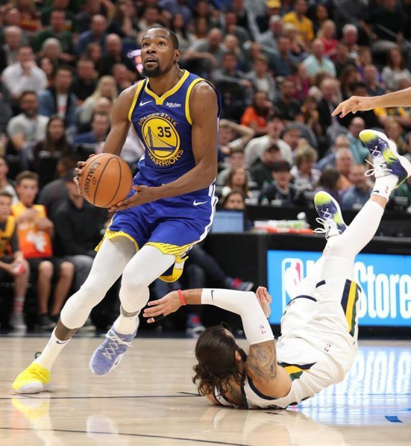 Ricky Rubio (d) de Utah Jazz cae al suelo en acción contra Kevin Durant (i) Golden State Warriors durante un partido de NBA. EFE/Archivo