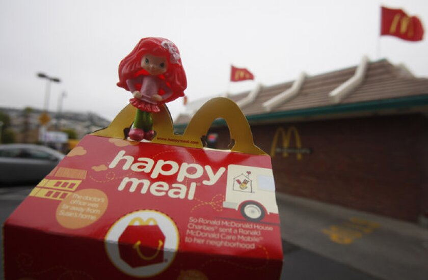 McDonald's has pledged to distribute 15 million books in its Happy Meals in England over the next two years.