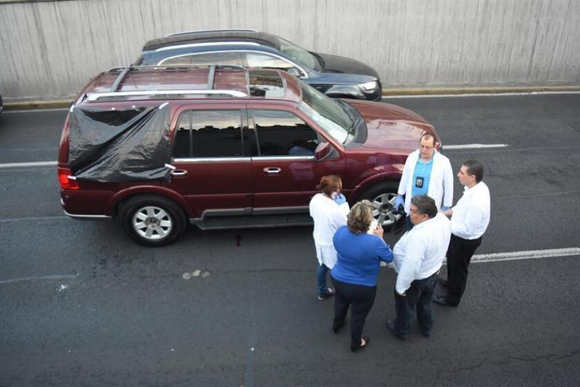 Fotografía que muestra a varios peritos forenses mientras inspeccionan el vehículo que fue abandonado en una vía rápida de Ciudad de México (México). En el interior del automóvil se hallaban dos hombres, uno sin vida y otro herido, presuntamente de nacionalidad colombiana. EFE/Archivo