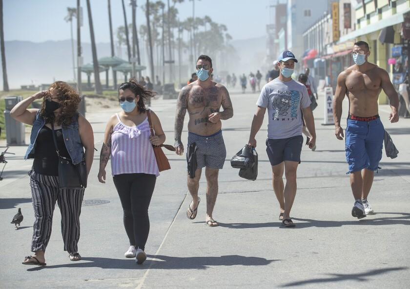 Pedestrians on Venice's Ocean Front Walk wear face coverings on May 14, the day after Los Angeles County reopened its beaches but kept many anti-pandemic measures in place.