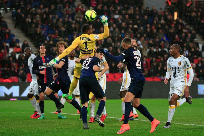Lille's goalkeeper Vincent Enyeama, center, punches the ball during his League One soccer match against Paris Saint Germain, at the Parc des Princes stadium, in Paris, Saturday, Feb. 13, 2016. (AP Photo/Thibault Camus)