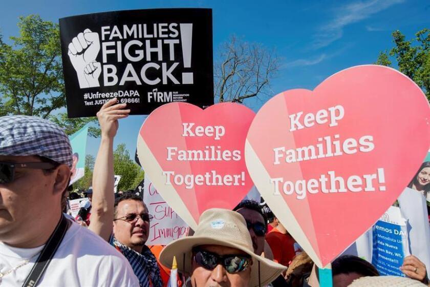 Decenas de personas sostienen carteles de apoyo a los inmigrantes afectados por los programas de Acción Diferida para Responsabilidad de los Padres (DAPA) y de Acción Diferida (DACA). EFE/Archivo