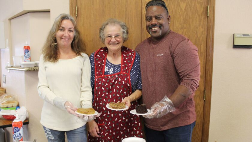 Manning the dessert table are AnnMarie Horan, event chair Ellen Sargent and Anthony Thomas.