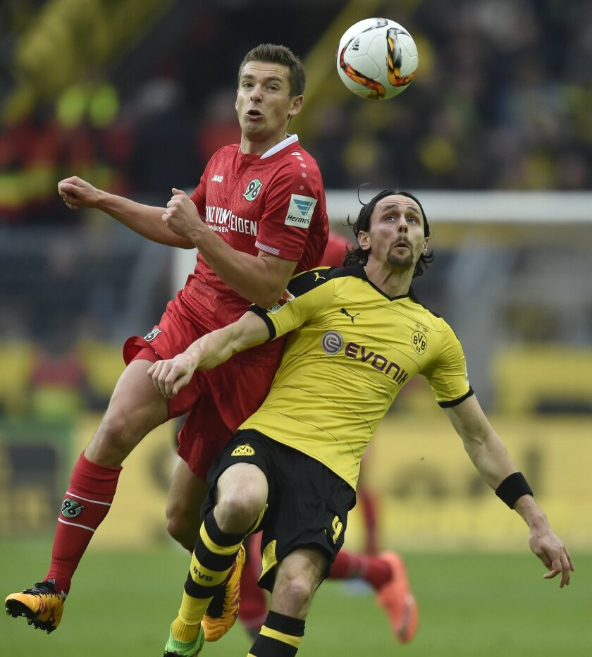 Hannover's Artur Sobiech, left, and Dortmund's Neven Subotic challenge for the ball during the German Bundesliga soccer match between Borussia Dortmund and Hannover 96  in Dortmund, Germany, Saturday, Feb. 13, 2016. (AP Photo/Martin Meissner)