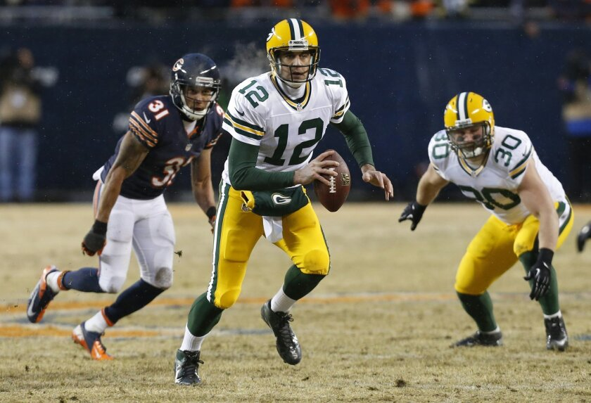 Green Bay Packers quarterback Aaron Rodgers (12) scrambles as he looks for a receiver during the first half of an NFL football game against the Chicago Bears, Sunday, Dec. 29, 2013, in Chicago. (AP Photo/Charles Rex Arbogast)