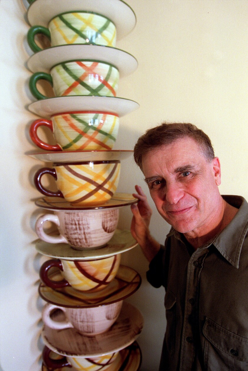 Curator Bill Stern poses with oversized coffee cups from  his ceramics collection in 2001.