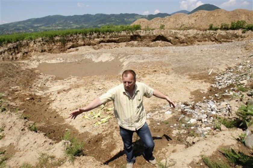Bosnian head of forensic team Murat Hurtic gesture as he shows original location where human bones were found in the eastern Bosnian town of Bratunac, 78 kms northeast of Sarajevo, Bosnia,on Wednesday, June 9, 2010. Experts say they found a wartime mass grave after a truck driver unloaded gravel next to a construction site and discovered human bones in the pile. Prosecutor Emir Ibrahimovic said Wednesday the driver reported his finding end of May and led the authorities to the site near the nearby town of Bratunac where he uploaded the gravel. Meanwhile witnesses have come forward claiming that a significant number of Muslims killed after Serb forces took control of Bratunac at the beginning of the 1992-95 war were secretly buried in gravel pit.(AP Photo/Amel Emric)