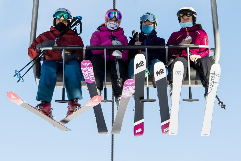 Skiers wearing face masks riding a chairlift.